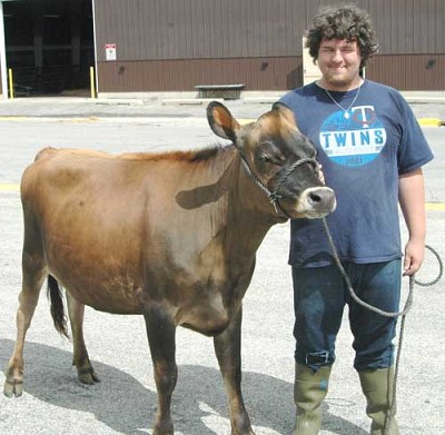 George Skare stands with �Comet,� a Jersey fall yearling, at the Olmsted County Fair.
