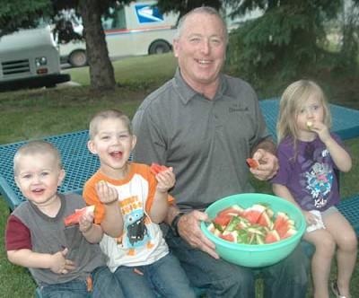 Mayor Jimmie-John King celebrated National Night Out by sharing a bucket of watermelon with three young friends at the Stewartville Public Library on Tuesday evening, Aug. 1. The children are, from left, David Daniels, 1; Nathan Daniels, 3; and Solara Gebhardt, 3, all of Stewartville.