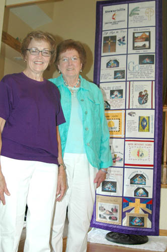 Renee Wilson, left, and Margaret Lex  stand with the embroidered banner highlighting the history of SUMC.