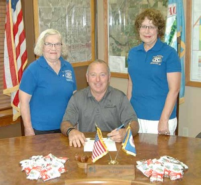 Mayor Jimmie-John King, seated in center, signs a proclamation declaring Sept. 8 and 9 Peanut Days in Stewartville. Janice Hagen, president of the Stewartville Kiwanis Club, standing at left, and Carol Youdas, club member, are two of the many club members who will accept donations to fight maternal and neonatal tetanus on those two days.