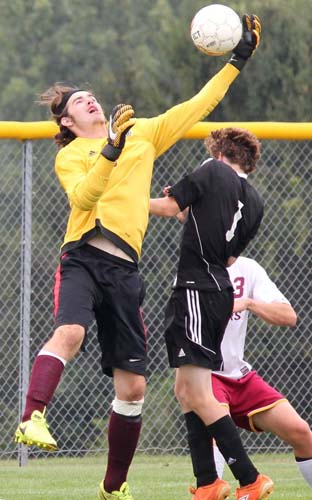 Tiger goal keeper Andrew Simmons leaps to rob a Bomber player and make a save during the Lake City Invite.