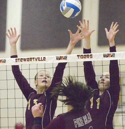 Erin Lamb (left) and Lily Welch block a Pine Island hitter during Stewie�s 3-0 sweep of the Panthers.