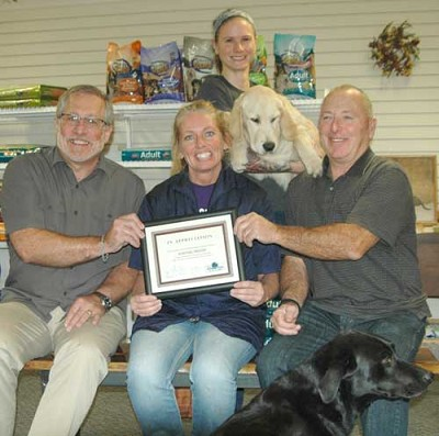 Jana Groski, seated in center, accepts the EDA�s Business Appreciation Award from Chris Stafford, EDA president, left, and Mayor Jimmie-John King, a member of the EDA. Kelley Smith, professional groomer, standing, holds Kumu, a golden retriever. Marley, a black Lab, is in the foreground.