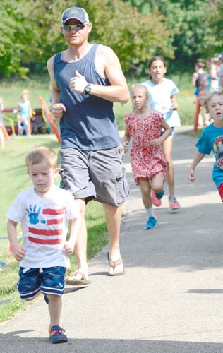 Micah Roeder, 3, sprints past his dad, Jon, as he crosses the finish line of the free half-mile Kids Fun Run.