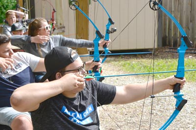 Participants at Ironwood Springs Christian Ranch�s National Wheelchair Sports Camp displaying their archery skills include, from front to back, Joe Lang of Loretto, Minn.; Danny Lilya of Moose Lake, Minn.; and Brynn Duncan of Moorhead, Minn.