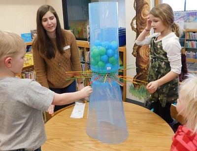 Sarah Schramek, an aide at the Stewartville Public Library, second from left, plays KerPlunk with, from left, Brody Blake, a pre-kindergarten Early Childhood Family Education Student at the Central Education Center; Lauren Blake, a first grader; and Shelby Blake, 2.